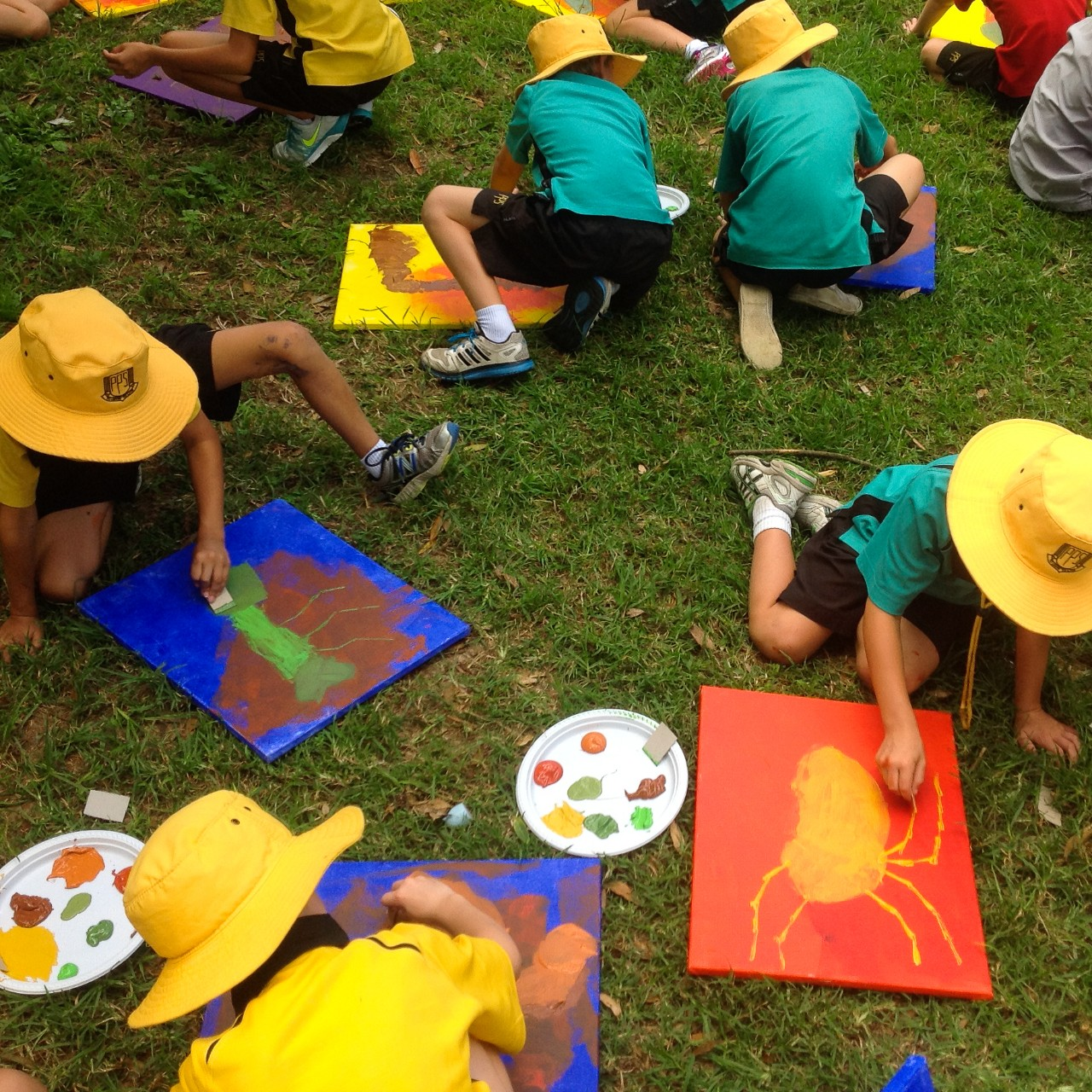 students painting on canvas outside