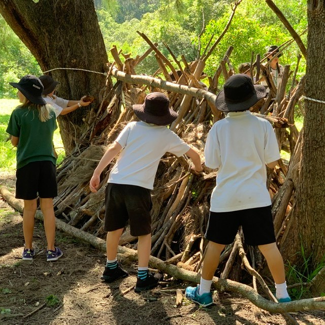 Children making fort with sticks and logs