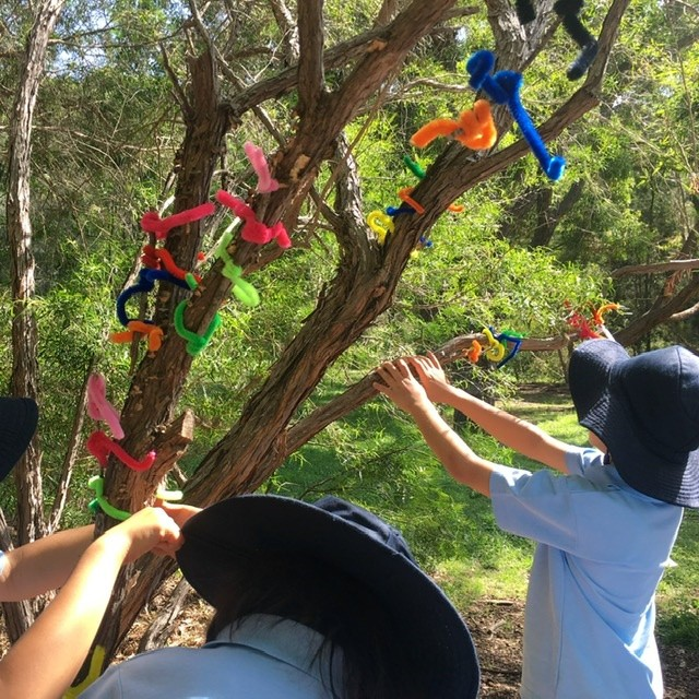 Children putting pipe cleaner stick insects in tree